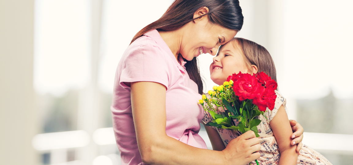 Girl giving mom flowers