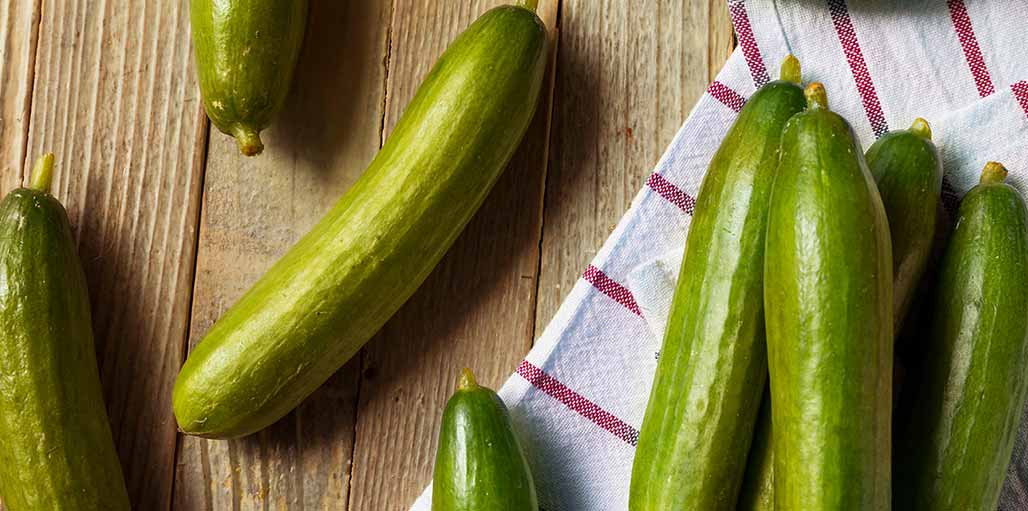 Cucumbers on worktop with red striped towel