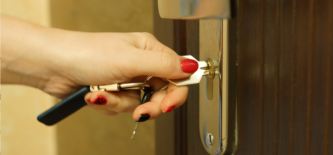 Woman with red and black nail varnish locking front door