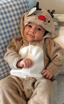 A baby in reindeer outfit