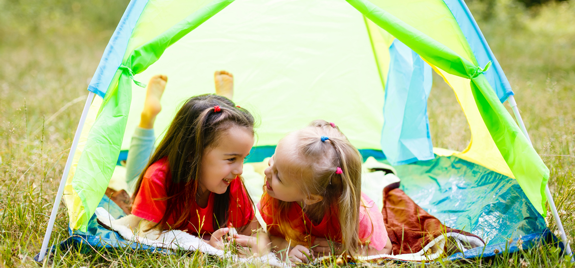 Children laying in a tent happy
