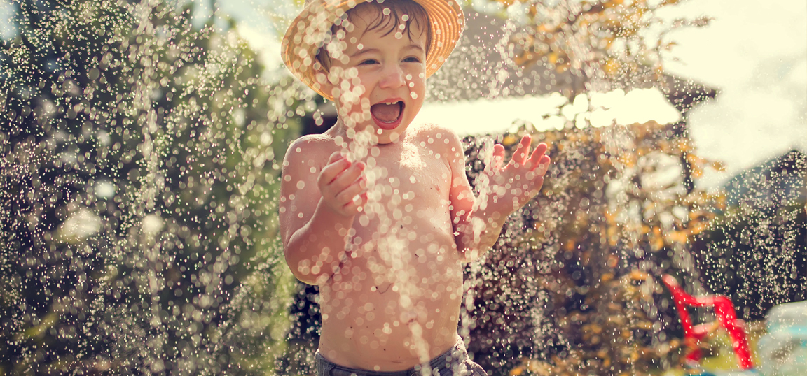 Child screaming with joy playing in water spray