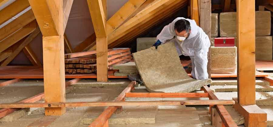 Man insulating a loft