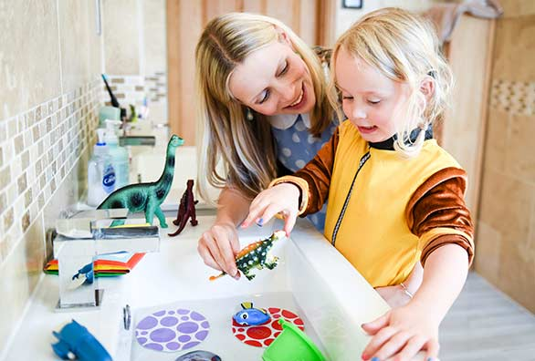 Happy mother and child playing with toys in the sink. HomeServe - Keeping homes happy with plumbing and drainage cover